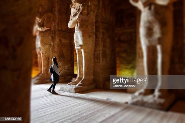 young millennial traveller tourist inside rameses ii temple in abu simbel between gigantic statues seems small - egyptian god stock pictures, royalty-free photos & images