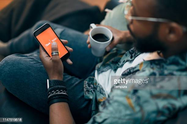 young millennial using technology for his investment and on line banking. - template stock pictures, royalty-free photos & images