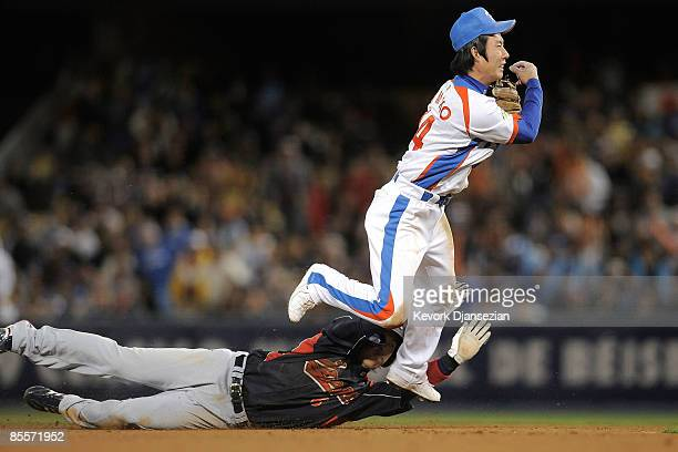 Young Min Ko of Korea turns the double play against Hiroyuki Nakajima Japan to end the seventh inning in the finals of the 2009 World Baseball...