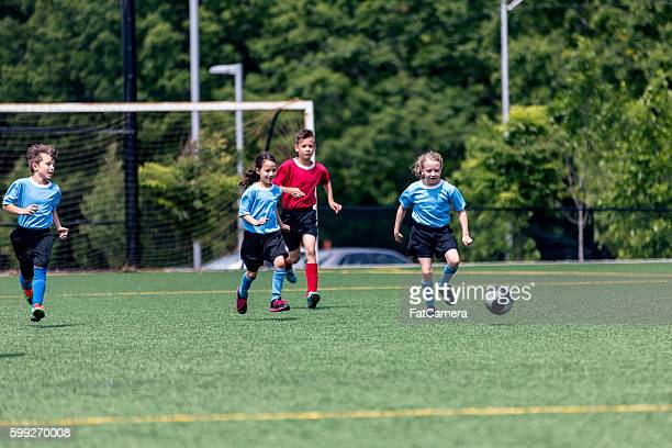Young mixed gender soccer team playing