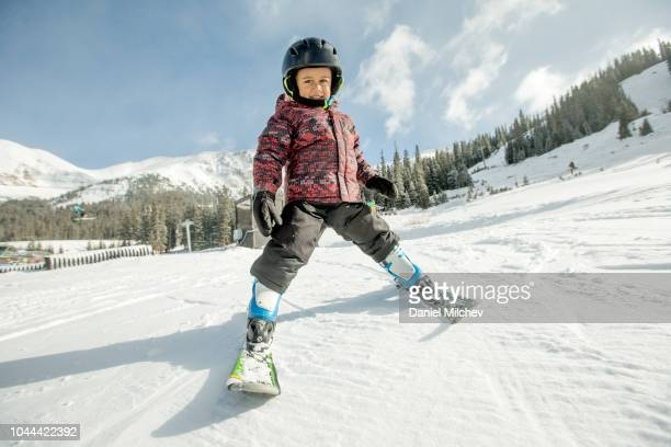 young mixed race boy learning how to ski at a winter resort in colorado. - winter sport stock pictures, royalty-free photos & images