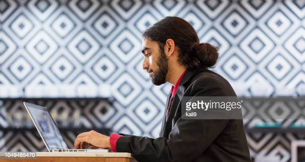 Young mixed race businessman using laptop computer