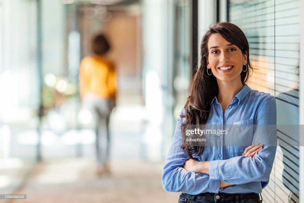 Giovane imprenditrice di razza mista sorridente alla telecamera : Foto stock