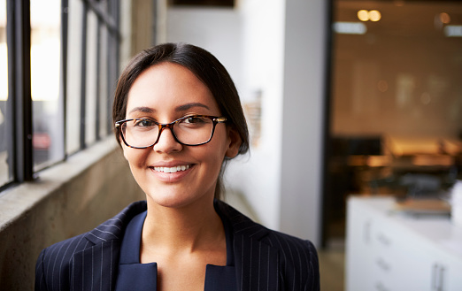 Young mixed race businesswoman wearing glasses, close up 1011797058