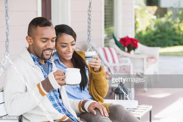 Junge gemischte Rennen paar Kaffeetrinken auf Veranda-Schaukel