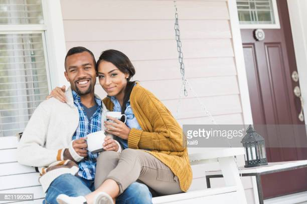Young mixed race couple drinking coffee on porch swing