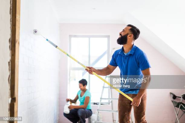 young mixed race couple painting their home - home improvement stock pictures, royalty-free photos & images