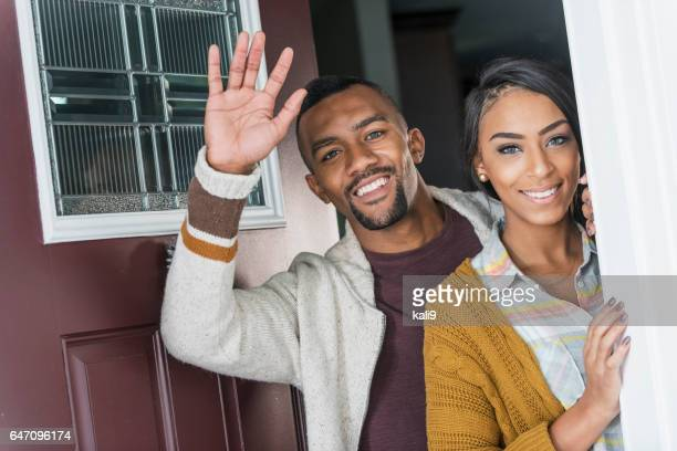 Young mixed race couple standing in front doorway waving