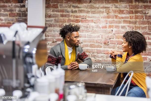 jong gemengd ras paar praten in de coffeeshop - afro amerikaanse etniciteit stockfoto's en -beelden