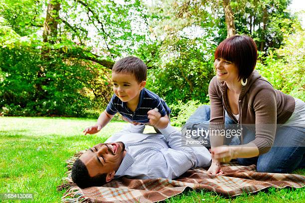 young mixed race family playing in the park - white wife black baby stock photos and pictures