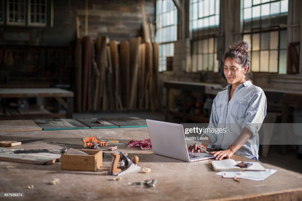 Young Mixed Race Female Entrepreneur Solving a Complicated Business Challenge with Pencil, Laptop, Carpentry Tools, and Confidence : Stock Photo