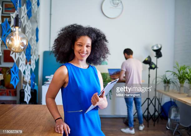 young mixed race female holding ipad looking to camera in modern sustainable office space. - sleeveless dress stock pictures, royalty-free photos & images