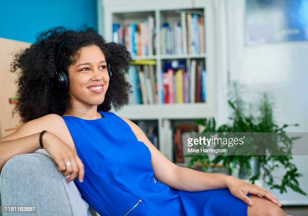 young mixed race female relaxing on chair at work in contemporary sustainable office space - sleeveless dress stock pictures, royalty-free photos & images
