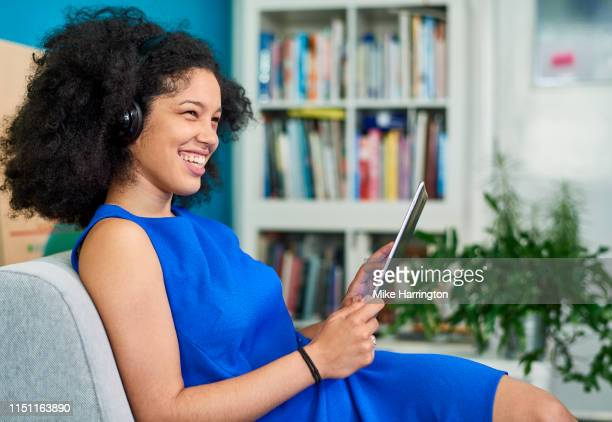 young mixed race female relaxing on chair at work with ipad in contemporary sustainable office space - sleeveless dress stock pictures, royalty-free photos & images