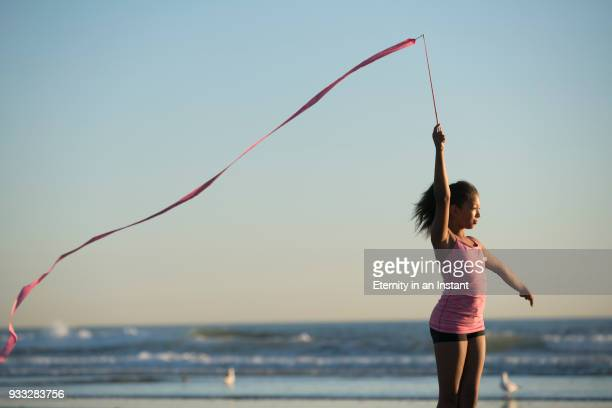 Young mixed race girl holding up a ribbon at sunset