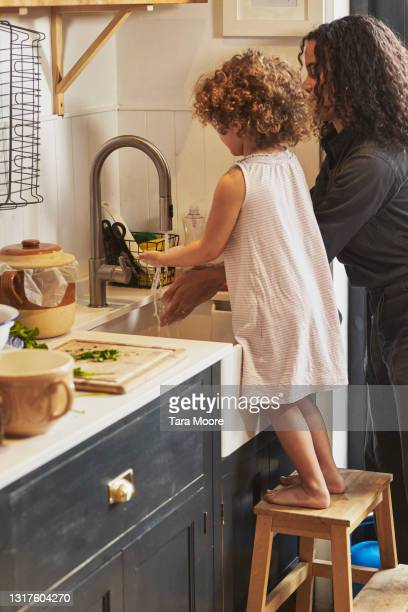 young mixed race girl in kitchen on a low stool washing her hands with mother. - clean stock pictures, royalty-free photos & images