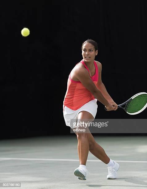 Young mixed race girl playing tennis