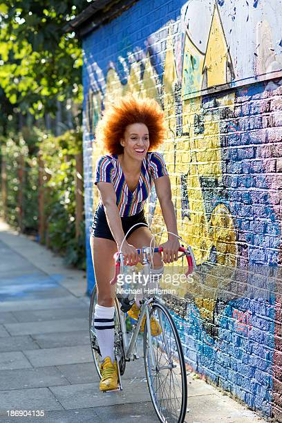 young mixed race girl smiling on bike - women wearing thigh high stockings stock pictures, royalty-free photos & images