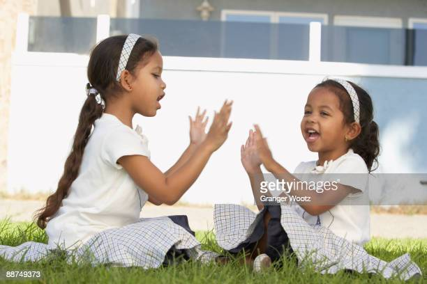 Young mixed race girls sitting and playing pat-a-cake