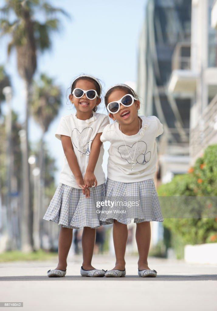 Young mixed race girls wearing sunglasses : Stock Photo