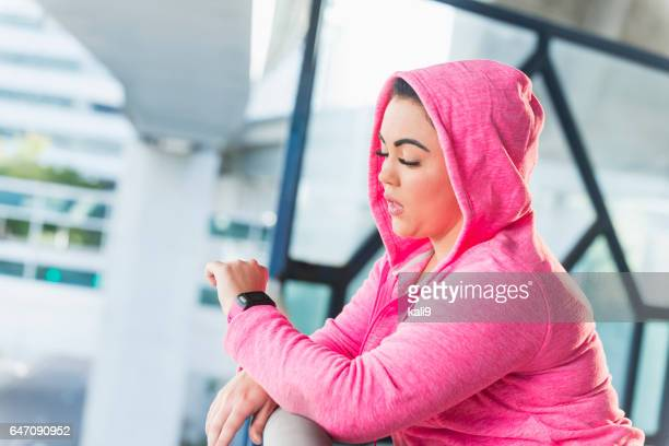 Young mixed race Hispanic woman with fitness tracker