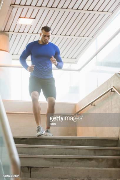 young mixed race man exercising, running down stairs - handsome native american men stock pictures, royalty-free photos & images