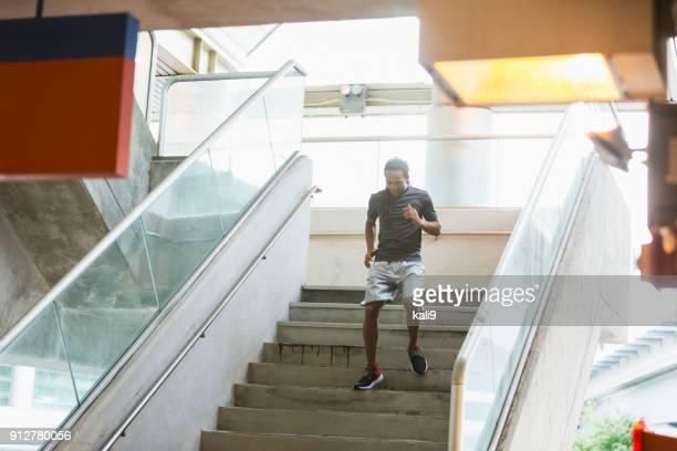 Jong gemengd ras man uit te oefenen, trap af lopen