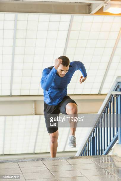 Young mixed race man exercising, running up stairs