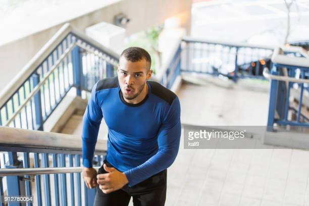 young mixed race man exercising, running up stairs - handsome native american men stock pictures, royalty-free photos & images