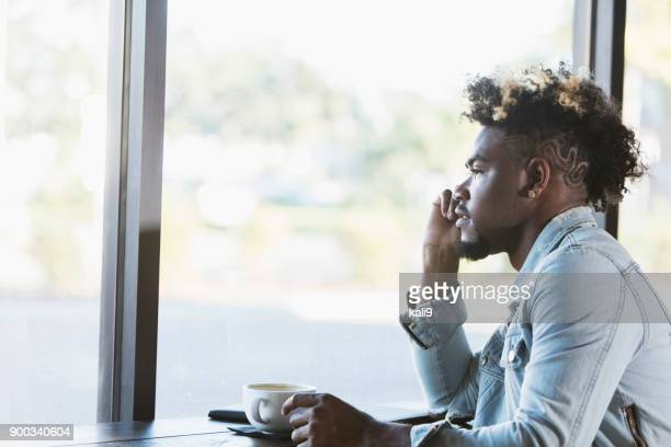 Young mixed race man looking out window in coffee shop