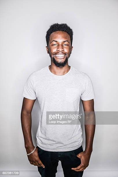 A young mixed race man posing in a studio looking happy