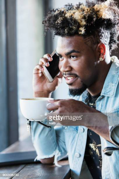 Young mixed race man sitting by window in coffee shop