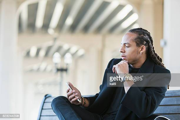 Young mixed race man staring at his mobile phone