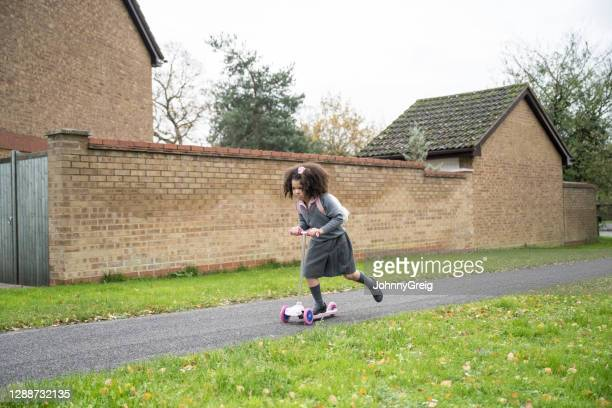 young mixed race student in uniform riding push scooter - determination stock pictures, royalty-free photos & images