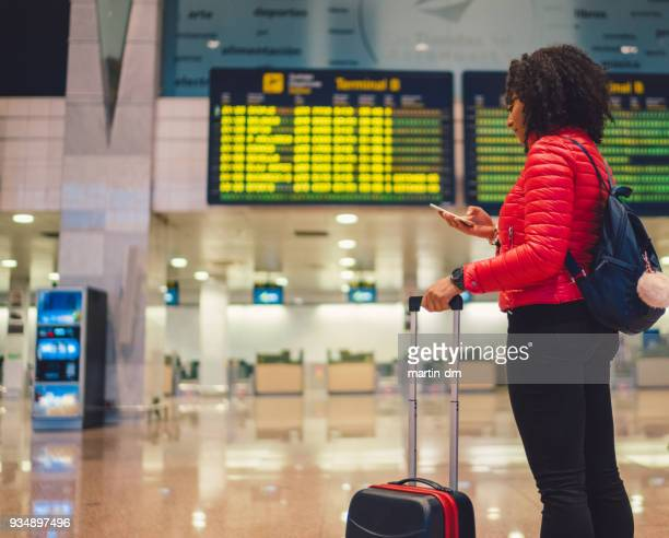 young mixed race tourist woman checking for flight at airport - heathrow stock pictures, royalty-free photos & images