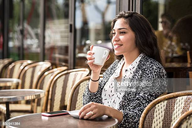 Young mixed race woman drinking coffee, smiling