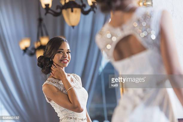 Young mixed race woman in elegant white dress