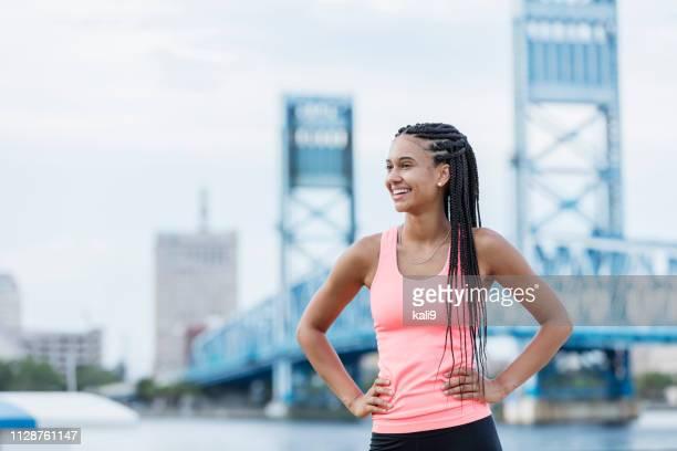 都市のウォーター フロントで若い混血女性 - コーンロウ ストックフォトと画像