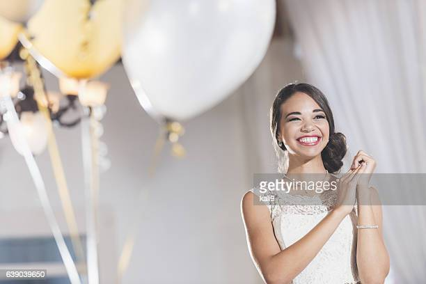 Young mixed race woman in white dress at party