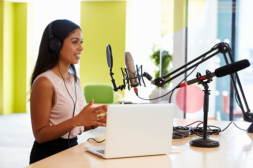 Young mixed race woman recording a podcast in a studio 869282570