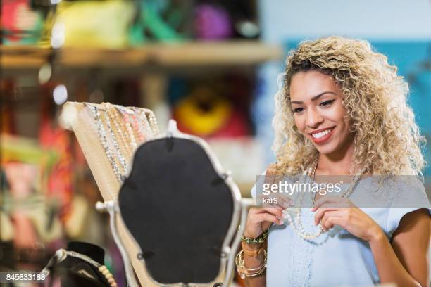 young mixed race woman shopping at jewelry counter - jewellery products stock photos and pictures