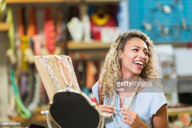 young mixed race woman shopping at jewelry counter - gift shop stock photos and pictures