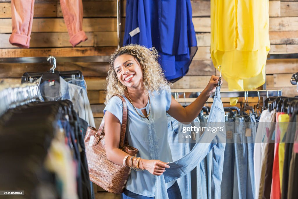Young mixed race woman shopping for clothing : Stock Photo