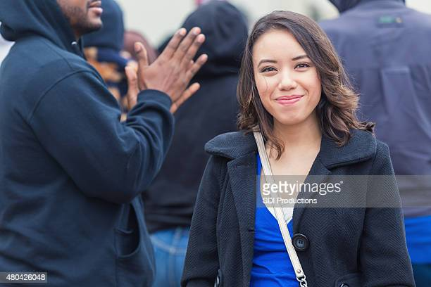 Young mixed race woman standing on crowded street in winter