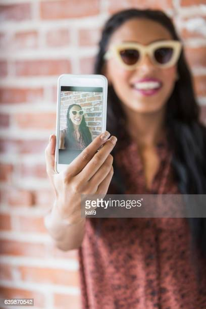 young mixed race woman taking selfie with mobile phone - holding aloft stock pictures, royalty-free photos & images