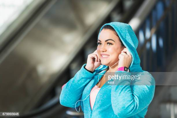 Young mixed race woman with earbuds and fitness tracker