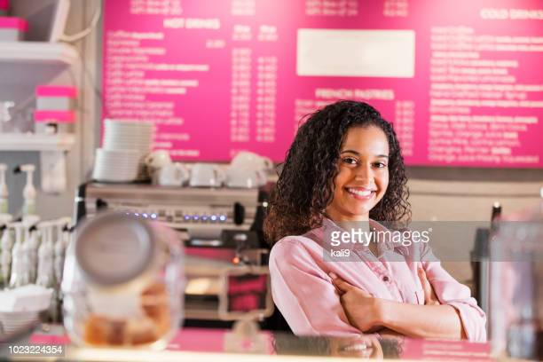 young mixed race woman working in coffee shop - franchising stock pictures, royalty-free photos & images