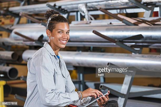 Young mixed race woman working in warehouse or factory