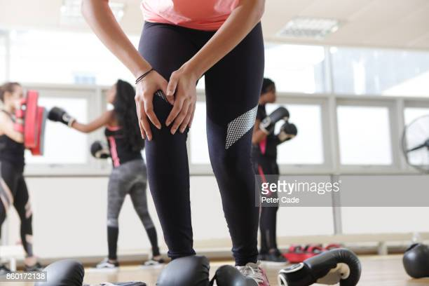 Young mixed race women in gym boxing, knee injury