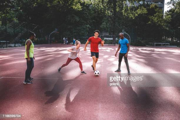 young mixed sports team playing soccer on hardcourt - small group of people stock pictures, royalty-free photos & images